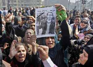 Demonstrators hold an image of Mohamed el-Gendy, a young activist tortured to death by police, 2013