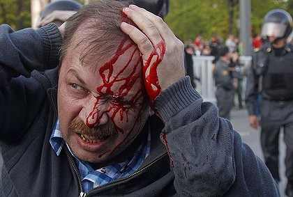 Demonstrator beaten by police at an anti-Putin rally, May 2012: © AP
