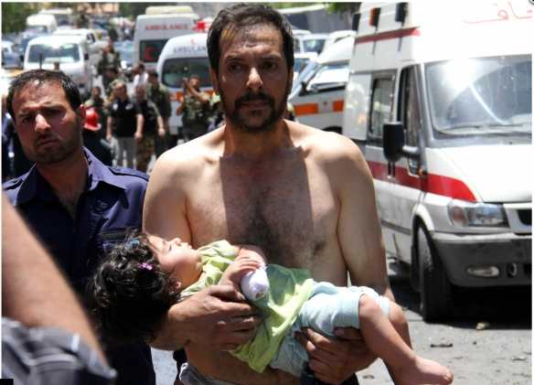 A man carries a wounded girl, after an explosion targeting a military bus in the Qudssaya neighborhood of Damascus, June 2012: AFP