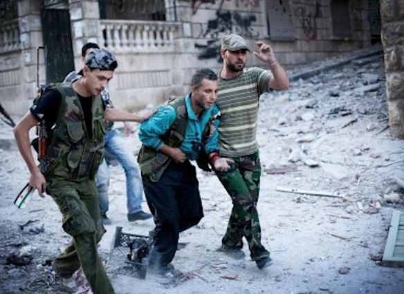 Free Syrian army soldiers help a fighter wounded by a Syrian army sniper, Aleppo, 2012: AP