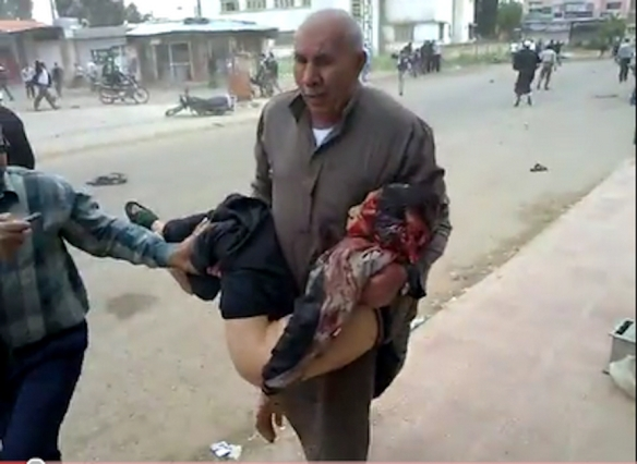 A man carries a wounded child away from an anti-Assad demonstration after regime forces opened fire, Syria, 2011