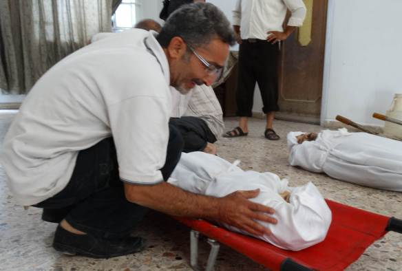 An image distributed by the opposition Shaam News Network, August 23, 2013, shows a relative mourning a family member killed during an alleged chemical attack in the eastern Ghouta area on the outskirts of Damascus