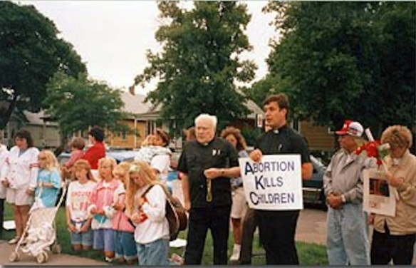 Father Paul Marx (center) leads protesters outside an abortion clinic