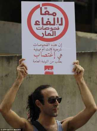 "Protester at 2012 Lebanese rally against forensic anal exams. ""Together against tests of shame: Whether anal or vaginal, they are rape on the prosecution's orders."""