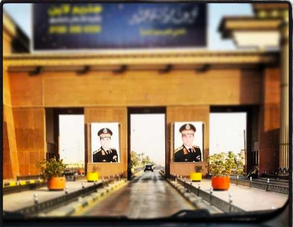 Abandon hope, all ye that think otherwise: Portraits of General Sisi at a toll booth on the Sokhna road, October 2013, from http://instagram.com/p/faSnnEGD-t/  (h/t @Seldeeb)