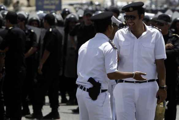 Black and white: Egyptian police officers joke, with Central Security anti-riot forces in the background: Reuters, 2012