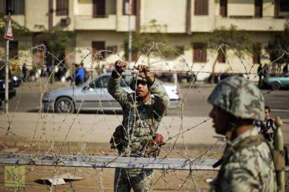 Soldiers set up barbed wire at a Cairo checkpoint