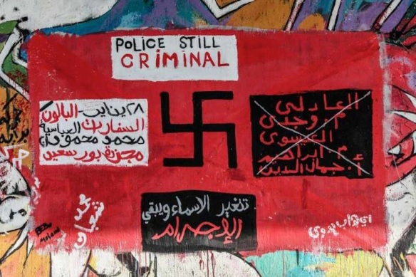 "Anti-police graffiti, Cairo. At bottom: ""The names change, the crime remains the same."" The left panel lists the sites of police massacres, the right panel lists Ministry of Interior officials."