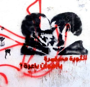 """The Revolution continues: the Brotherhood brings shame."" 2013 anti-Morsi graffiti showing a suspiciously homoerotic kiss between Egypt's embattled President and the Brotherhood's Supreme Guide, Mohammed Badie."