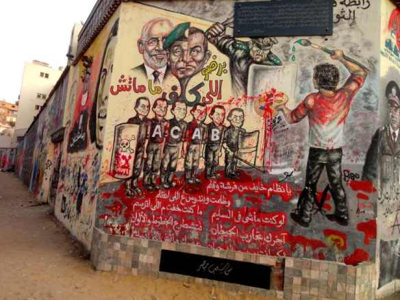 "Anti-police graffiti in Cairo. At top: ""Those who appoint a successor never die."" a parody of a proverb. At bottom: ""O system! You're afraid of a pen and brush. ... You long to fight with walls, to have power over lines and colors."" ACAB: ""All cops are bastards."""