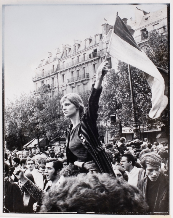 Woman waving flag in crowd during general strike demonstration, Paris, May 1968: by Jean-Pierre Ray