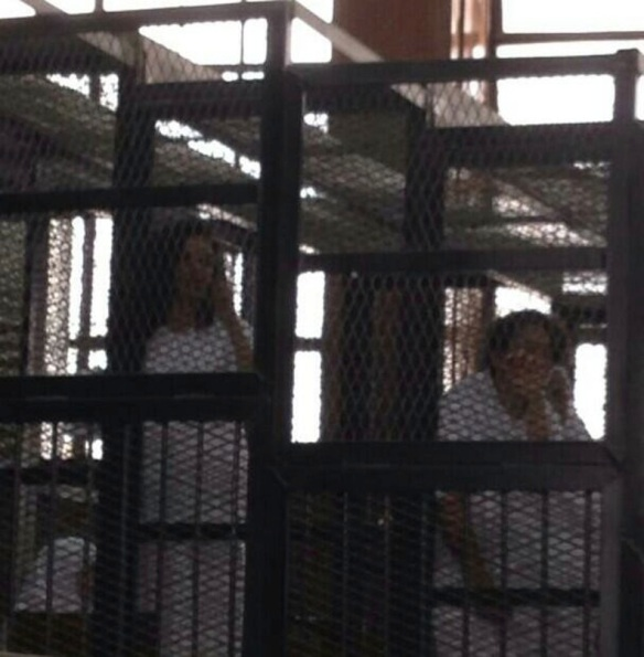 Yara Sallam (R) in the courtroom cage in Tora, June 23