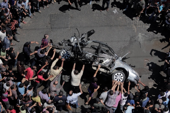 Palestinians inspect a car destroyed in an Israeli air strike in central Gaza City, July 8, 2014. Photo: Ali Jadallah / APA images.