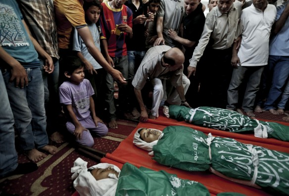 Palestinian mourners gather around the bodies of three siblings of the Abu Musallam family -- Ahmed, 11; Walaa, 14; and Mohammed, 16 – killed by an Israeli shell in Beit Lahiya, northern Gaza Strip, July 18, 2014. Photo: Lefteris Pitarakis/Associated Press.