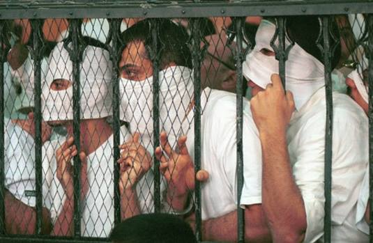 Prisoners in the courtroom cage during the Queen Boat trial wear masks to protect themselves from sensation-seeking photographers: Cairo, 2001