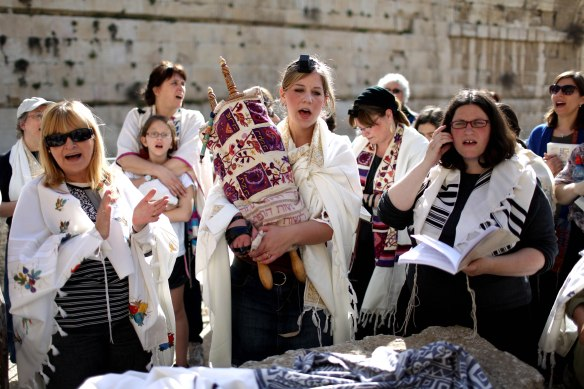 Dangerous and anti-Israel: Woman carries a Torah scroll at An Israeli Jewish woman carries a Torah scroll in prayers near the Western Wall,  March 2013. Photos: EPA/Abir Sultan