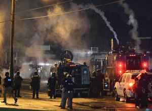 Pollice with armored personnel carriers fire tear gas at protesters, Ferguson, Missouri, August 17, 2014. Photo: Roberto Rodriguez/EPA