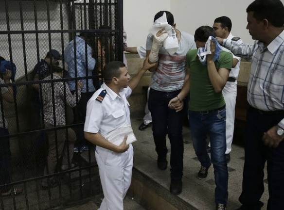Convicted men in the wedding video trial cover the faces as police lead them from the courtroom cage, Cairo, November 1, 2014: Photo © Independent (UK)
