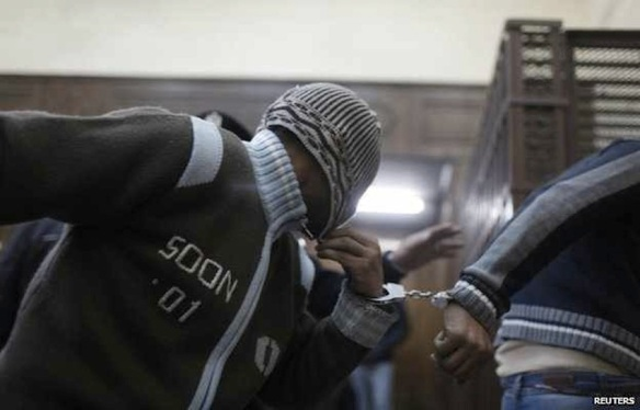 Covering their faces, shackled defendants are dragged into court, January 12: Photo by Reuters