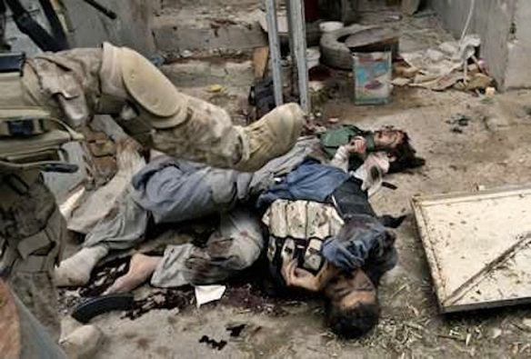 A US Marine pushes corpses of Iraqi fighters, Fallujah, Friday, November 12, 2004. Photo by Anja Niedringhaus / Associated Press