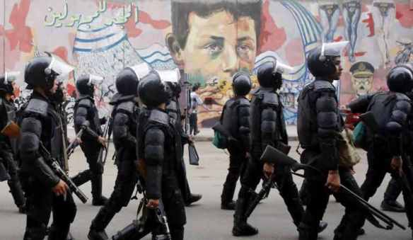 "Egypt's finest: Central Security forces march along Mohamed Mahmoud Street in central cairo, under graffiti reading ""Glory to the Unknown,"" November 19, 2014. Photo by Amr Abdallah Dalsh for Reuters"