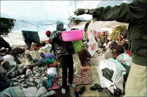 A Sudanese removes rainwater from a tarp in the protest camp, December 25, 2005. Five days later police attacked the camp. Photo by Shane Baldwin, New York Times