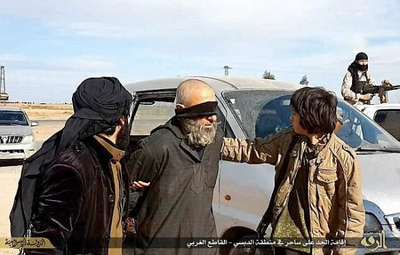 """A man is led to execution for """"invoking magic"""" in a village near Raqqa, February 2015. Photo from ISIS-affiliated social media"""