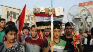 Protesters carry national flags and an electric fan in Baghdad, August 7, 2015. Photo by Karim Kadim/AP