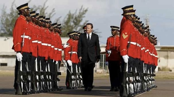 No sudden moves. I'm surrounded by black men with knives. Cameron tiptoes gingerly through honor guard on arriving in Jamaica.