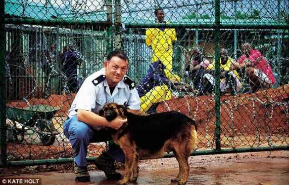 Will Thurbin, former governor of an Isle of Wight prison, poses at Montagne Posse Prison in Seychelles with his dog Lucy, while Somali prisoners behind razor wire look on. Photo by Kate Holt for the Daily Mail