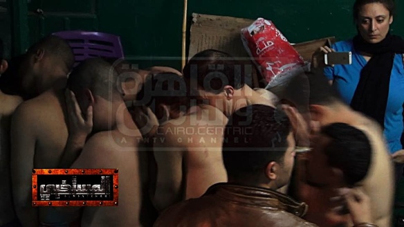 Mona Iraq, upper right, films her stripped victims being led to police wagons, December 7, 2014. Later that night she posted this photo on her Facebook page.