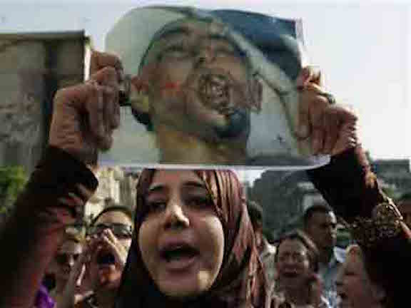 A woman carries an image of Khaled Said, tortured to death by police, at a 2010 Egyptian protest against his murder